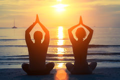Silhouettes of man and woman meditation on sunset beach. Silhouettes of men and women meditation on sunset beach. Yoga and health Royalty Free Stock Image