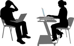Silhouettes of man and woman working on their laptops