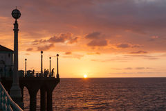 Silhouettes on Manhattan Beach pier watching sunset sunset Calif. Silhouettes of people gathered to experience sunset over ocen from Manhattan Beach pier Stock Image