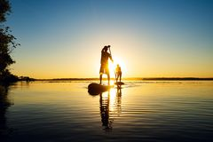 Silhouettes men, friends who are paddling on a SUP boards. On a large river during sunrise. Stand up paddle boarding - awesome active recreation in nature stock photography