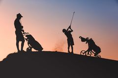 Man with his son golfers silhouette. Silhouettes of men with his son golfers playing golf on golf course at sunset Stock Images