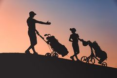 Man with his son golfers silhouette royalty free stock photography