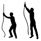 Silhouettes of men pulling ropes Stock Image