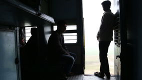 Silhouettes of men in train hall by open door during a train ride. stock footage