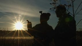 Silhouettes of men and women against the background of the sun. Slow motion. stock footage