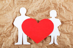 Silhouettes of men, women and heart cut out of paper. Stock Image