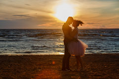 Silhouettes of men and women in the lush short skirt, kissing ag. Ainst the sea and the Golden sunset Stock Photos