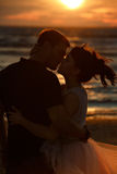 Silhouettes of men and women in the lush short skirt, kissing ag. Ainst the sea and the Golden sunset Royalty Free Stock Image