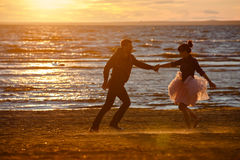 Silhouettes of men and women in the lush short skirt, running ac Royalty Free Stock Photography