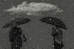 Silhouettes of men and women under umbrellas Royalty Free Stock Photo