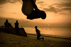 Silhouettes of men working out on the beach Royalty Free Stock Images