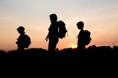 Silhouettes of mom hiking with her kids at sunset. Silhouettes of family hiking at sunset. Happy family on summer vacation in mountains. Mom and kids carry stock photo