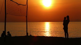 Silhouettes of mom and kid standing at volleyball net at sunrise stock footage