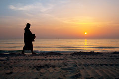 Silhouettes of monks on Hua Hin beach Stock Photo