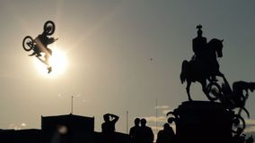 Silhouettes of monument, group of people standing underneath and jumping bikers. stock video footage