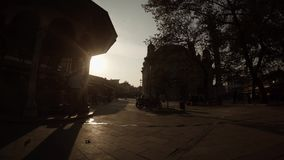 Silhouettes of a mosque, motorcycles and passers-by in the rays of the evening sun in the center of a Turkish city. KONYA / TURKEY - 11.20.2016 central streets stock video footage