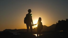 Silhouettes of mother and child tourists hiking at sunset. Mom and daughter on summer vacation carrying backpacks. Little girl following her mom on cliff edge stock video
