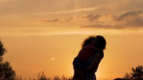 Silhouettes of mother and daughter hugging against beautiful evening sky, love