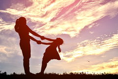 Silhouettes mother and  daughter playing and hugging Stock Photography