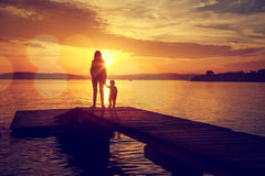 Silhouettes of Mother and Her Son by the Lake Stock Images