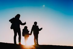Silhouettes of mother with kids enjoy hiking at sunset. Silhouettes of mother with kids enjoy hiking in sunset nature Stock Photography