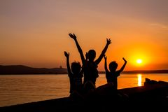 Silhouettes of mother and kids at sunset. At the beach stock photo