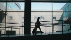 Silhouettes of mother and little daughter going down the gate at the airport at background large window stock footage