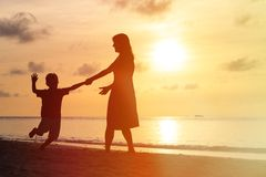 Silhouettes of mother and son having fun at sunset Royalty Free Stock Image