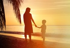 Silhouettes of mother and son holding hands at Stock Images