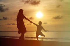 Silhouettes of mother and son playing at sunset Royalty Free Stock Image