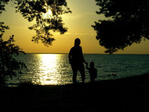 Silhouettes of mother and son on the sea beach at sunset Royalty Free Stock Image