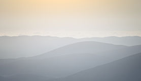 Silhouettes of mountain slopes in the haze Stock Photo