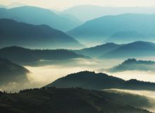 Silhouettes of mountains. A misty autumn morning. Dawn in the Carpathians Stock Photos