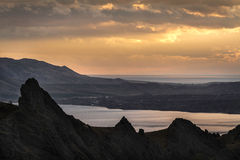 Silhouettes of mountains at sunset on a background of the cloudy Stock Photography