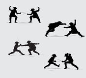 Silhouettes Musketeers. Two silhouettes fighting with swords Musketeers Royalty Free Stock Photography