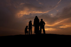Silhouettes of a muslim women with her kid. During sunset Royalty Free Stock Photos