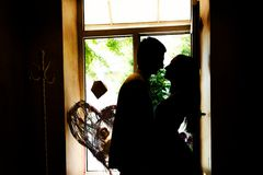 Silhouettes of the newlyweds in the cafe stock images
