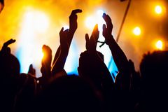 Silhouettes Of Concert Crowd In Front Of Bright Stage Lights. Unrecognized People In Crowd. Copy Space Background. Crowd Of Fans A Stock Photos