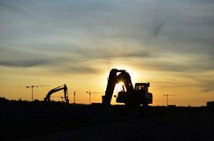 Free Silhouettes Of Excavators At A Construction Site Against The Background Of Tower Cranes And Sunset. Royalty Free Stock Photography - 157690327