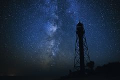 Silhouettes of the Old Lighthouse sandy beach and ocean against the background of the starry sky.  Stock Image