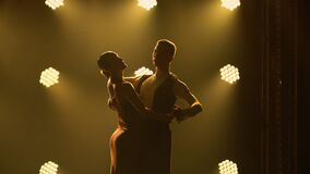 Silhouettes of a pair of dancers performing elements of Argentine dance appear against the smoky yellow background of