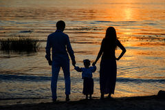 Silhouettes of parents and child on the background of the setting sun Stock Photos
