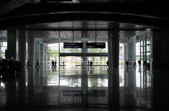 Silhouettes of passengers go on a station Stock Images