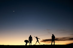 Silhouettes of people against the night sky Stock Image