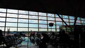 Silhouettes of people in the airport terminal. They hurry on their flight and on business. Silhouettes of people in the airport terminal. They hurry on their stock video footage