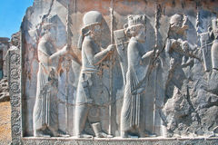 Silhouettes of people in ancient costumes on the destroyed stone bas-relief Stock Image