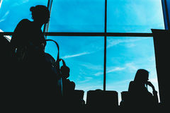 Silhouettes of people on the background of a window in the waiting room at the airpor Royalty Free Stock Images