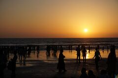 Silhouettes of People on Beach at Sunset Stock Photos