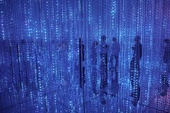 Silhouettes of people behind a curtain of electric blue garlands. Floor mirrors. Silhouettes of people behind a curtain of electric garlands. Floor mirrors stock image