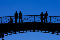 Silhouettes of People on Bridge Royalty Free Stock Image